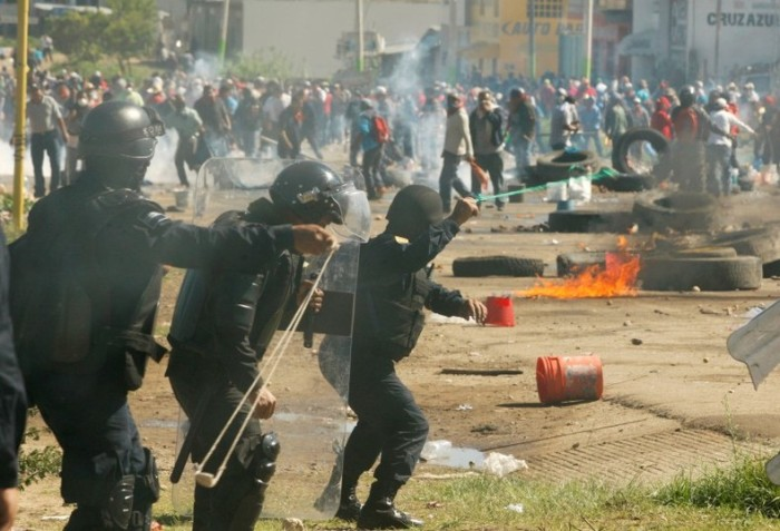 Protesters from the National Coordination of Education Workers (CNTE) teachers' union clash with riot police officers during a protest, in Nochixtlan